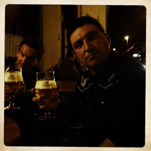 Paul and Steve sitting at a pub holding glasses of beer