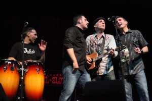 Three band members around one mic with Chris on congas